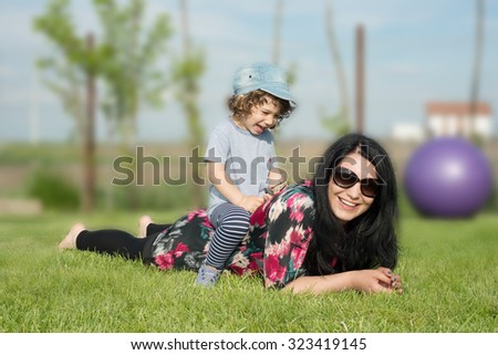 Mother and son having fun outside,boy sitting on mother back - stock photo