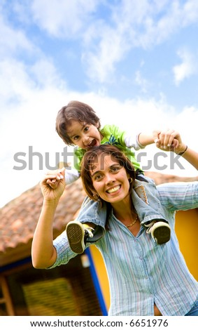 mother and son having fun portrait at home outdoors - stock photo