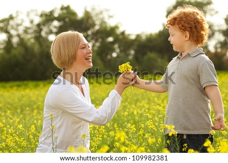 Mother and Son Having Fun. Son giving flowers to his mother. outdoor shot. - stock photo