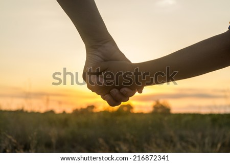 Mother and son holding hands into the sunset of a summer day - stock photo