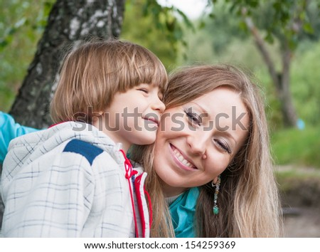 Mother and son hugging outdoors, focus on mum - stock photo