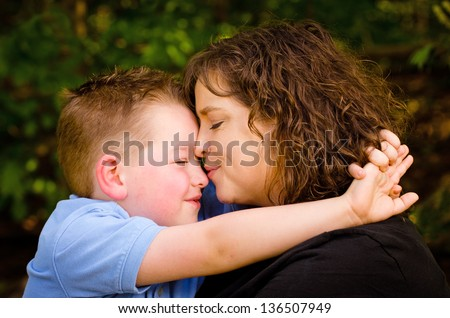 Mother and son hugging with woman kissing child - stock photo