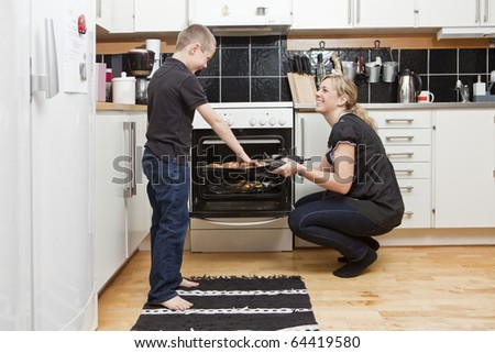 Mother and son in a kitchen situation - stock photo