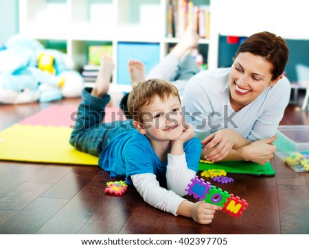 Mother and son in a play room together. - stock photo