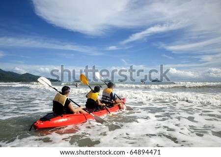 Mother and son in an ocean going kayak.tropical island in the Maldives or Thailand coconut palms on the beach in the Indian Ocean. Andaman Sea