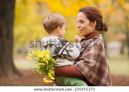 Mother and son in autumn park carrying flowers - stock photo
