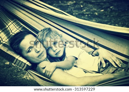 Mother and son in garden hammock together  - stock photo