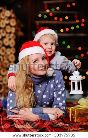 Mother and son in red caps of Santa Claus on a background  Christmas lights