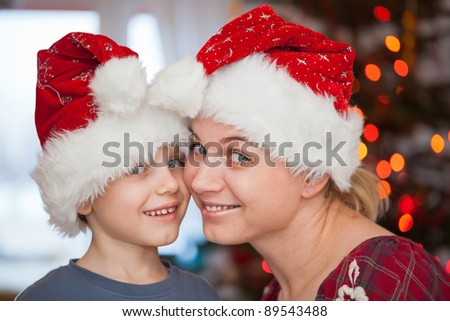 Mother and son in santa clause hats having fun in christmas day - stock photo