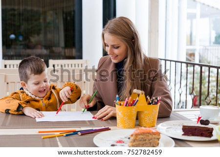 mother and son in the restaurant painted pencils before eating