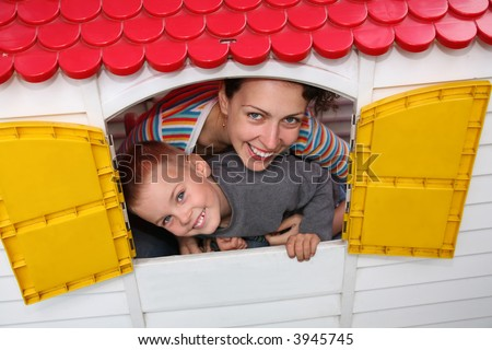 mother and son in the toy house - stock photo