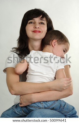 Mother and son in white t-shirts and jeans tightly hugging - stock photo