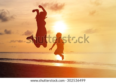 mother and son jumping at sunset beach, happy family - stock photo