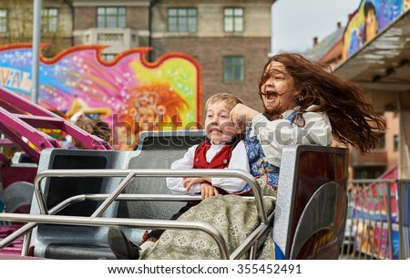 Mother and Son laughing in a carousel in an amusement park. - stock photo