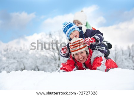 Mother and son laying down in the snow - stock photo