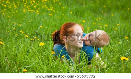 Mother and son laying on the green grass - stock photo