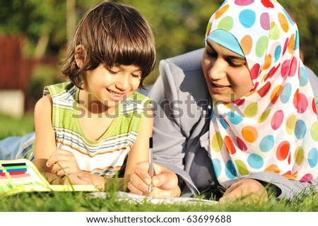 Mother and son learning together in nature, muslim - eastern cultural islamic clothes - stock photo