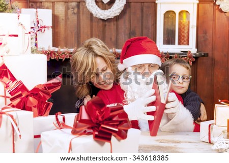 mother and son look at wish list with santa claus