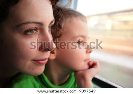 mother and son look in train`s window - stock photo