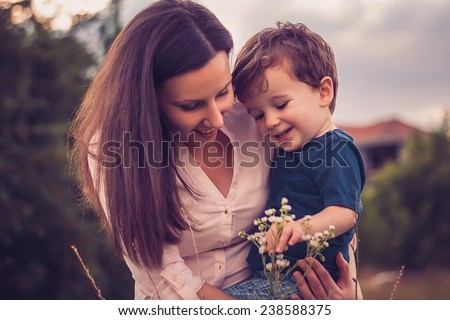 Mother and son looking at flowers - stock photo