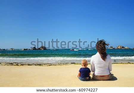 Mother and son looking at the waves on the beach of the Atlantic, France