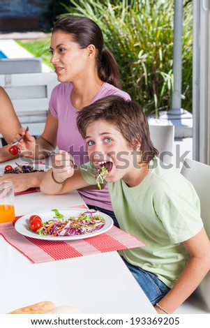 mother and son lunch, eating happy smile, pretty woman with little boy sitting at home dinner table restaurant or cafe - stock photo