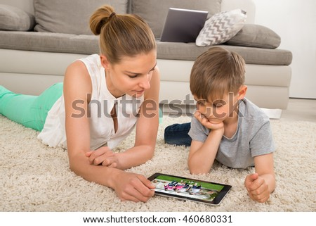 Mother And Son Lying On Carpet Watching Movie On Digital Tablet At Home