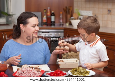 Mother and son making pizza together at home