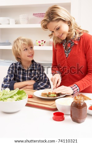 Mother And Son Making Sandwich In Kitchen - stock photo
