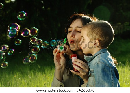 Mother and son making soap bubbles outdoors in the summer park - stock photo
