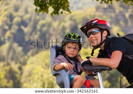 Mother and son on a cycling trip using safety devices (helmets, child seat). Shallow DOF. - stock photo