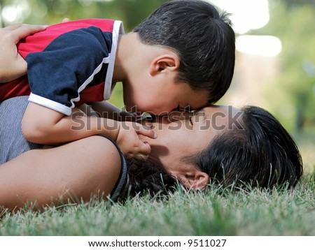 Mother and son on grass - stock photo