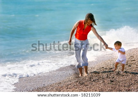 mother and son on pebble beach - stock photo
