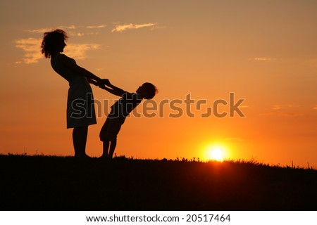 Mother and son on sunset holding by hands