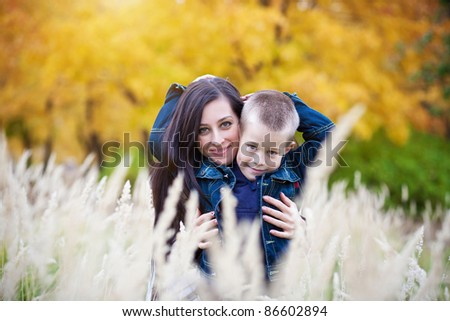 Mother and son on the autumn meadow - stock photo