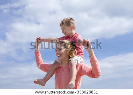 Mother and Son on the background of bright blue sky. They are laughing and smiling.