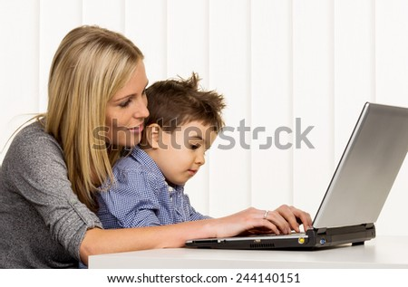 mother and son on the computer, symbol of home, family and career, double burden - stock photo