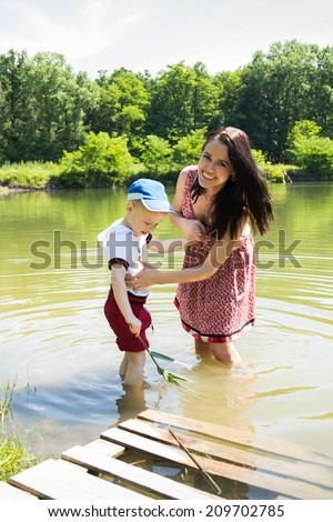 Mother and son on the lake. Standing knee-deep in water, cool in hot weather and communicate with each other.Nature, lake, swimming, baby - The concept of country vacation. article about the rest.