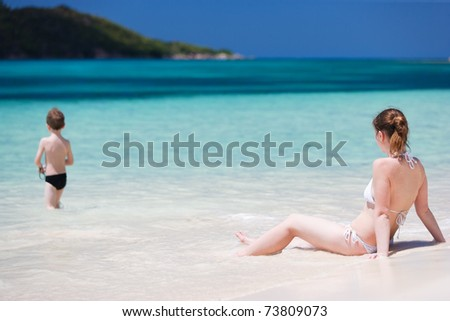 Mother and son on tropical beach vacation - stock photo