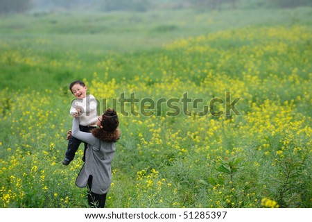 mother and son outdoor in flowers - stock photo