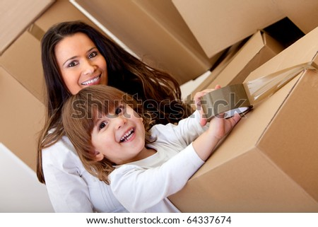 Mother and son packing into cardboard boxes and smiling