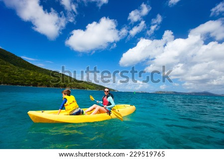 Mother and son paddling on colorful yellow kayaks at tropical ocean water during summer vacation - stock photo