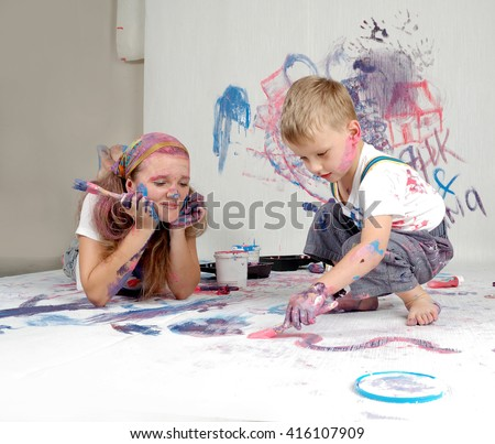 Mother and son paint the walls and floor. Children's creativity. Art for baby. Mother and child repair the room. - stock photo