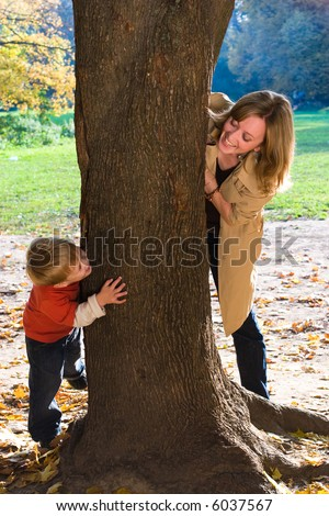 Mother and son play hide-and-seek in autumn park - stock photo