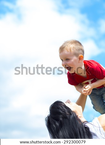 Mother and Son play in the field - stock photo