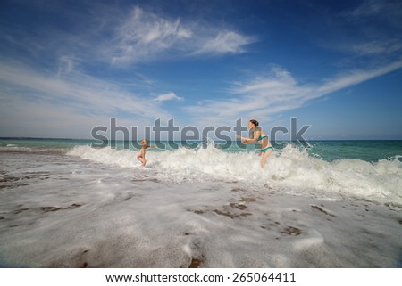 Mother and son play in the waves on the beach - stock photo