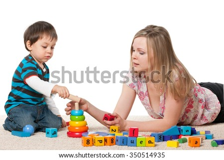 Mother and son play on the carpet with blocks - stock photo