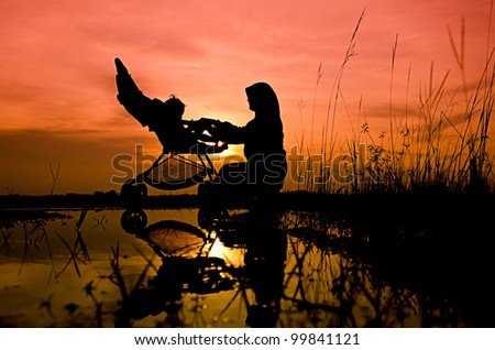 Mother and son playing at lake garden during sunset - stock photo