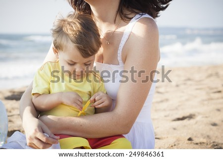 Mother and son playing at the beach - stock photo