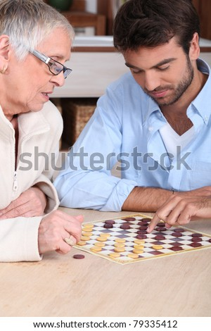 Mother and son playing checkers - stock photo